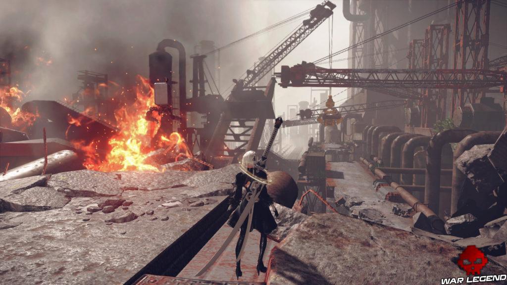 Aperçu NieR Automata héroïne devant paysage industriel, flammes sur sa gauche